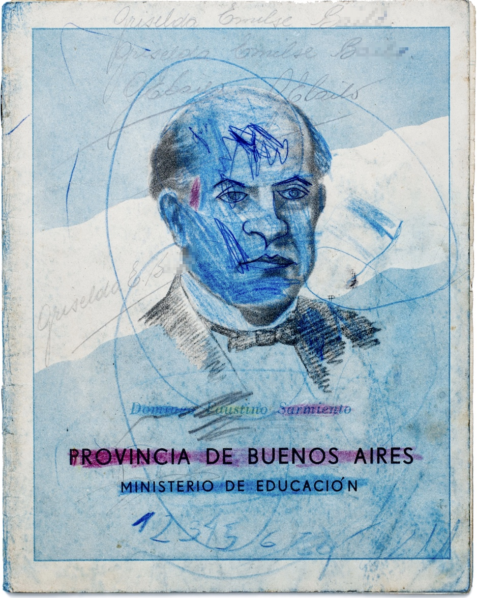A photo of the cover of a child's exercise book. It has a portrait of a man printed on it that has been scribbled over by the child.