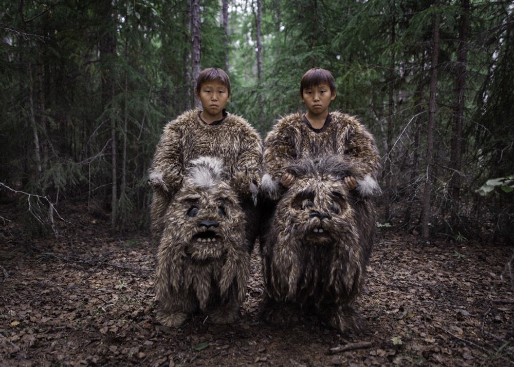 A photo of two men standing in a forest. They are wearing large, furry suits that appear to be for some kind of giant animal or perhaps monster and are holding the heads of the suits in their hands so you can see their faces, looking deadpan at the camera.