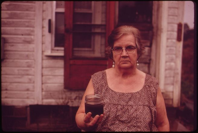 erik_calonius_-_mary_workman_holds_a_jar_of_undrinkable_water_that_comes_from_her_well_and_has_filed_a_damage_suit_against_the_hanna_coal_company_._101973.jpg